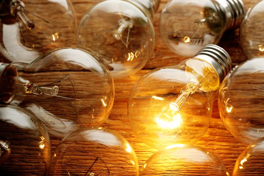 lit light bulb among unlit ones on wood
